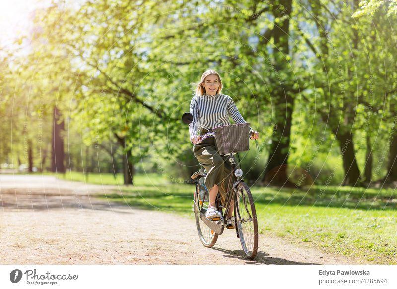 Junge Frau radelt durch den Park grün Bäume Natur Frische genießend Lifestyle jung Erwachsener Menschen lässig Kaukasier positiv Glück Lächeln attraktiv schön