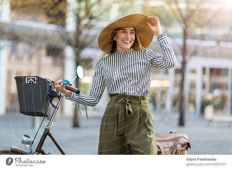Junge Frau steht mit ihrem Fahrrad in der Stadt Strohhut Feiertag Urlaub Mode Park grün Bäume Natur Frische genießend Lifestyle jung Erwachsener Menschen lässig