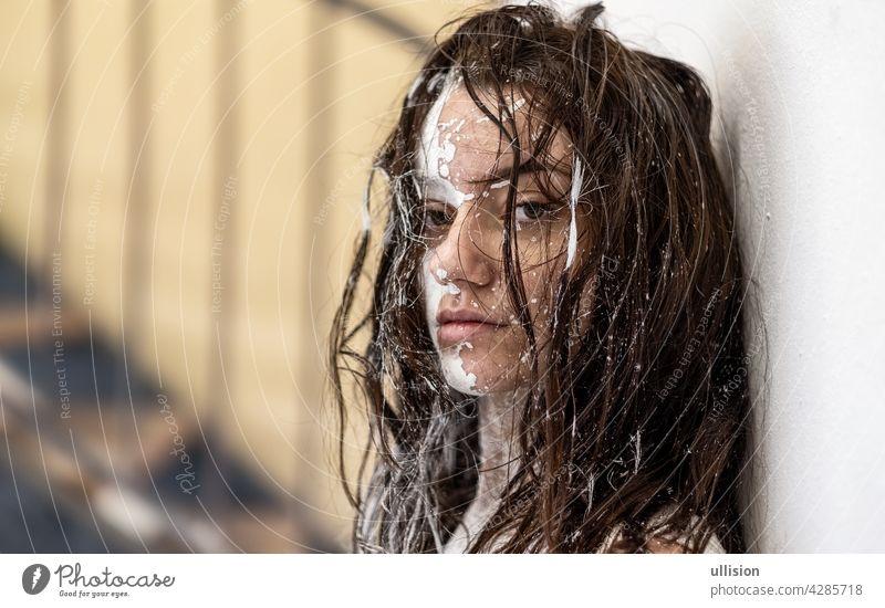direkte Ansicht Porträt einer sexy jungen Frau mit dunkelbraunem Haar, in weißer Farbe gemalt dekorativ. Kreative expressive Körper Malerei Kunst, Make-up, Kopie Raum.