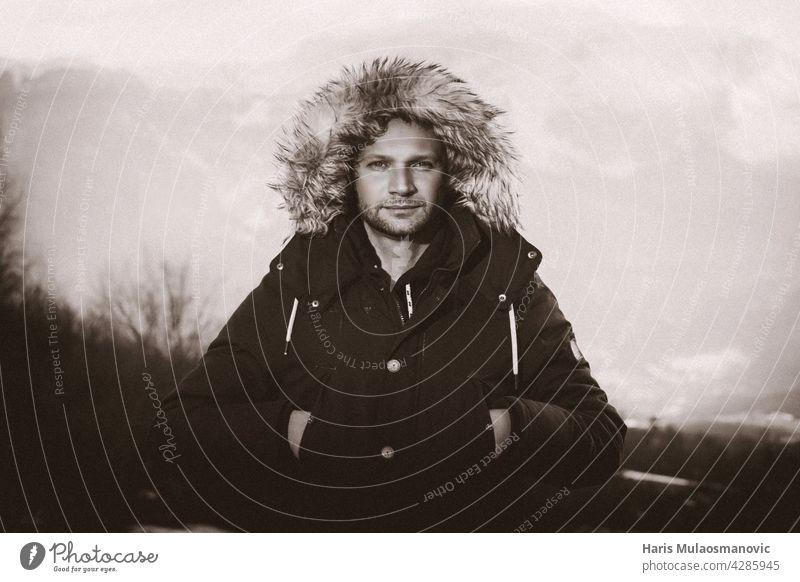 Porträt eines Mannes in Schwarz und Weiß in Jacke Winterzeit schwarz auf weiß Berge u. Gebirge Schwarzweißfoto im Freien