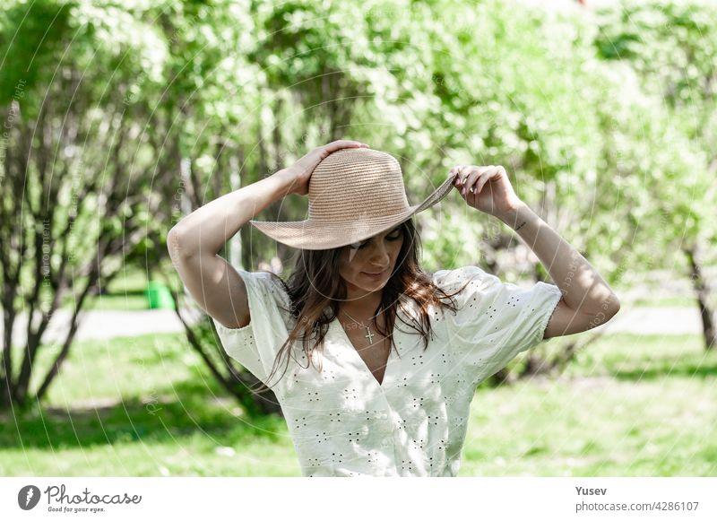 Junge schöne glückliche Frau in modischen Strohhut. Eine brünette Frau in einem weißen Hemd stehen im Freien und hält ihren Hut mit den Händen. Blühende Frühling Apfelbaum Park Hintergrund. Sonniger Sommertag