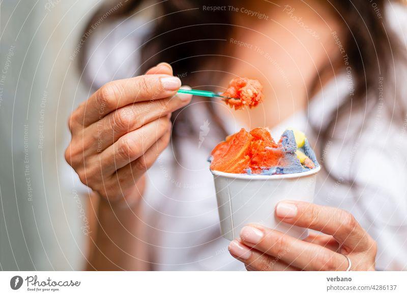Frau hält einen Becher mit regenbogenfarbenem Eis Eiscreme Hand Essen hispanisch frisch Straßenessen Menschen smartwatch Hände Frucht Beteiligung lgbt Farben