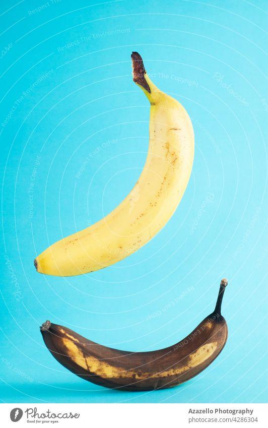 Frische und faule Bananen auf blauem Hintergrund. Echtes Foto von einer frischen Banane schwebend ob blauem Hintergrund. Ackerbau Veganer Gesundheit gelb alt