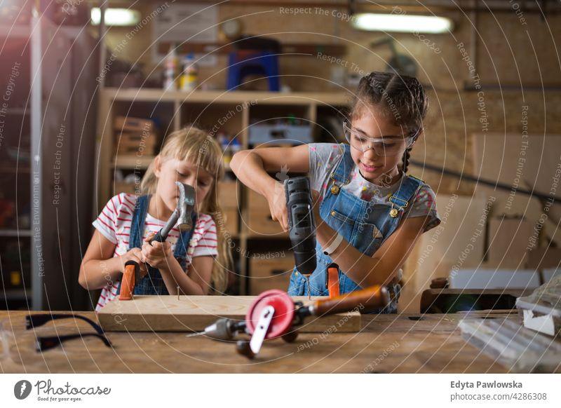 Kinder arbeiten in der Werkstatt Menschen Mädchen Frauenpower Fähigkeit Handwerk Garage Hobby Lifestyle Werkzeuge Konzentration Kreativität Präzision Zimmerer