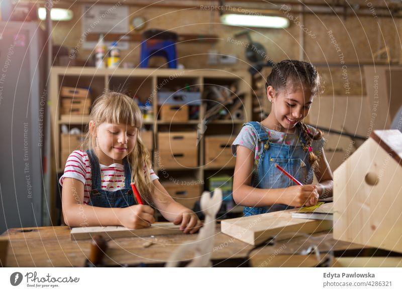 Zwei junge Mädchen bei der Holzarbeit in einer Werkstatt arbeiten Menschen Kind Kinder Frauenpower Fähigkeit Handwerk Garage Hobby Lifestyle Werkzeuge