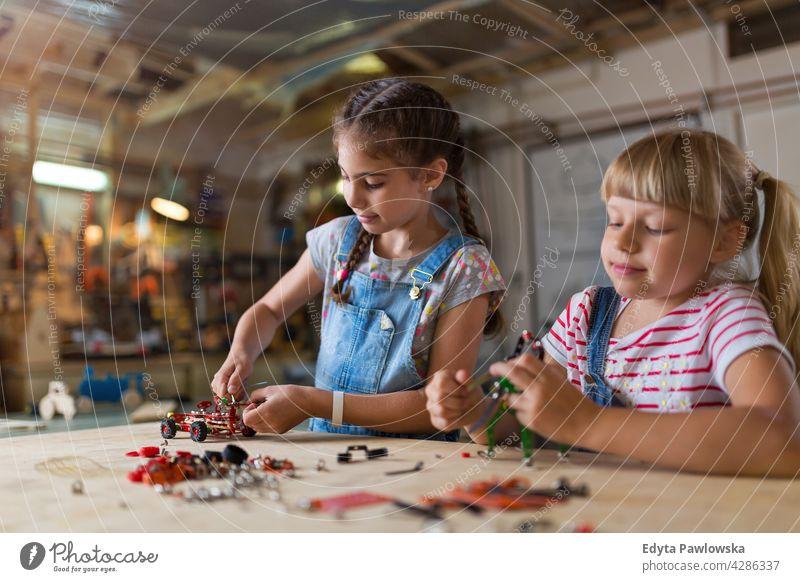 Kleine Mädchen bauen Spielzeug Baumaschine Werkstatt Lernen Menschen Kind Kinder Frauenpower Fähigkeit Handwerk Garage Hobby Lifestyle Werkzeuge Konzentration