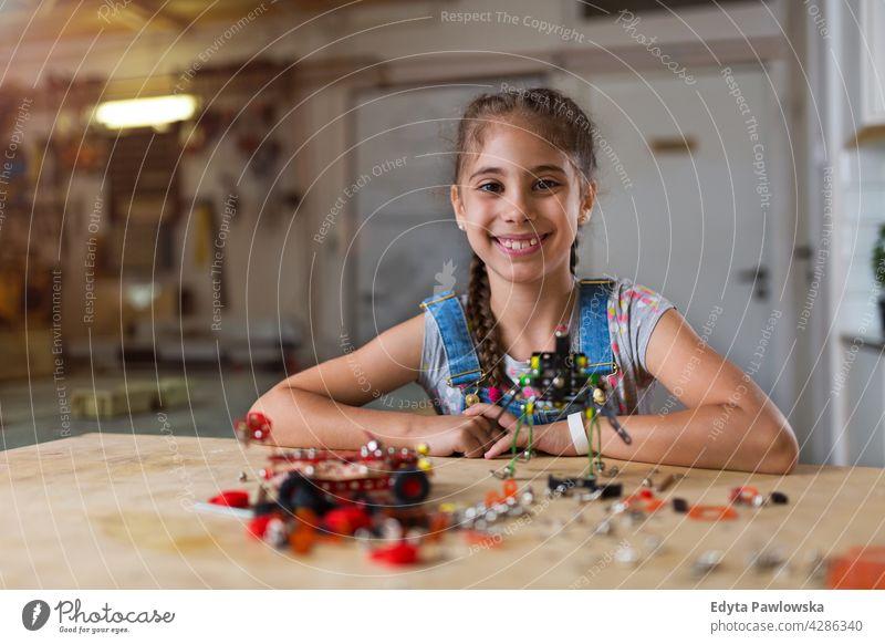 Kleines Mädchen baut einen Roboter Werkstatt Lernen Menschen Kind Kinder Frauenpower Fähigkeit Handwerk Garage Hobby Lifestyle Werkzeuge Konzentration