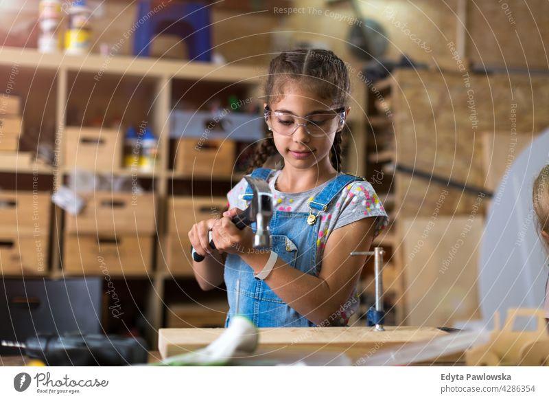 Junges Mädchen bei Holzarbeiten in einer Werkstatt Menschen Kind Kinder Frauenpower Fähigkeit Handwerk Garage Hobby Lifestyle Werkzeuge Konzentration