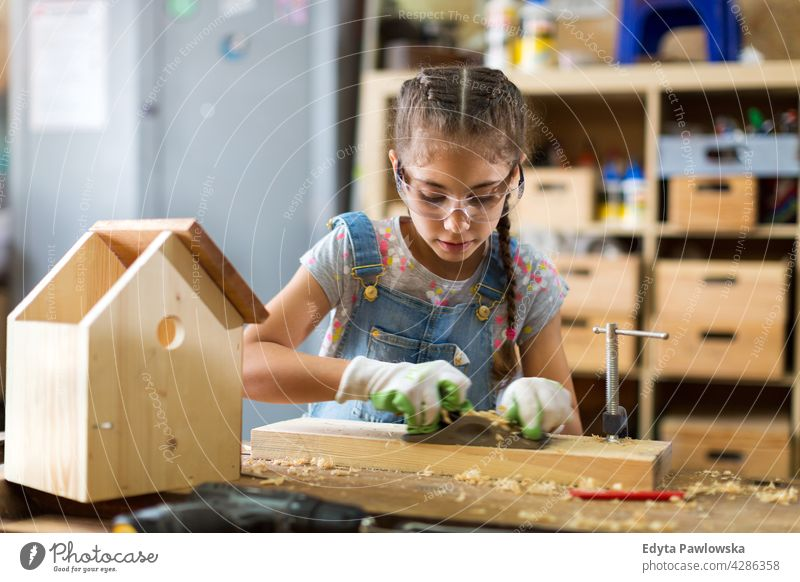 Mädchen baut Vogelhaus in Garage Werkstatt arbeiten Menschen Kind Kinder Frauenpower Fähigkeit Handwerk Hobby Lifestyle Werkzeuge Konzentration Kreativität