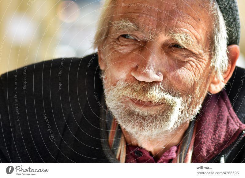 verschmitzt, gewitzt und guter Dinge Mann Porträt bärtig Senior weißhaarig Vollbart Gesicht schmunzeln Runzeln freundlich gutgelaunt Lächeln Bart