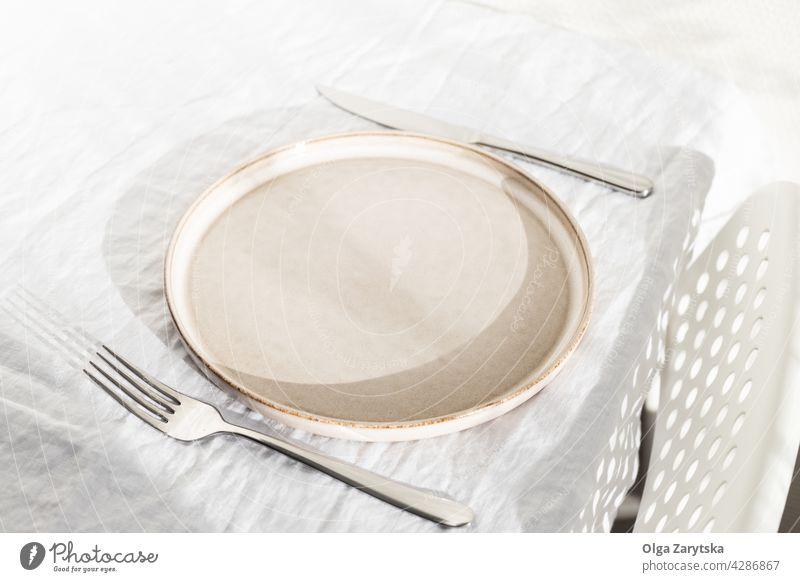Leerer Teller auf weißem Leinentischtuch. leer Einstellung Tisch Tischwäsche Sonnenlicht niemand Winkelansicht sehr wenige Stuhl Wand Küche