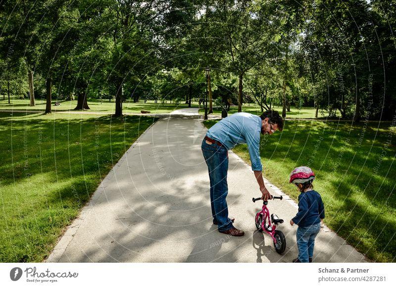 Papa übt mit Kind Laufrad fahren Tochter Elternzeit Ausflug Helm lernen Park Natur Vater Zusammensein Familie & Verwandtschaft Mädchen Sommer