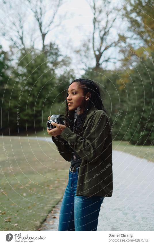 Junges Mädchen mit Kamera feminin Junge Frau Jugendliche 18-30 Jahre Erwachsene Freizeit & Hobby Fotografieren Leichtigkeit schwarz fokussieren Außenaufnahme