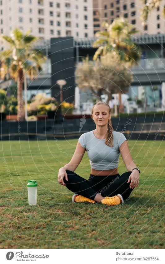 Eine junge Frau sitzt im Lotussitz auf dem Rasen im Park neben dem Haus und meditiert nach einem Workout. Sport, Fitness, Yoga. Gesunder Lebensstil Konzept