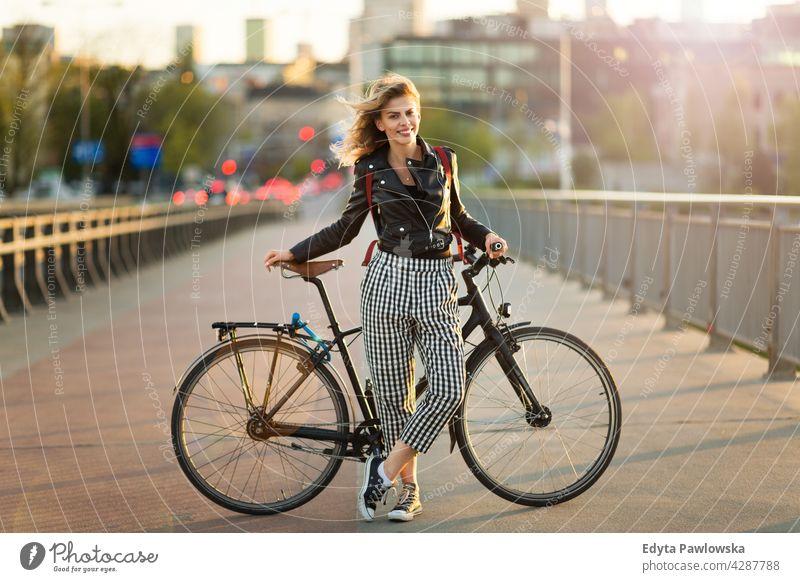 Attraktive junge Frau steht mit ihrem Fahrrad in der Stadt genießend Lifestyle Erwachsener Menschen lässig Kaukasier positiv Glück Lächeln attraktiv schön Tag