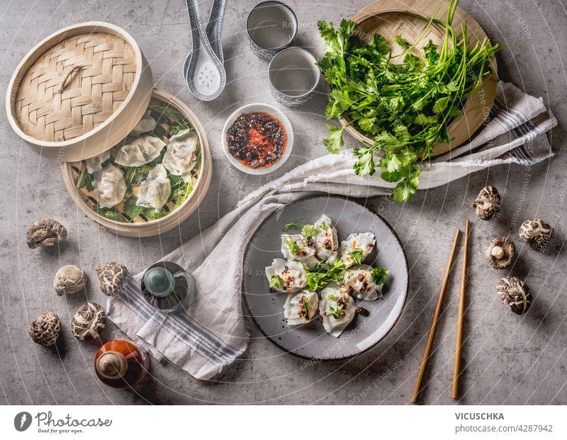 Asiatisches Essenskonzept mit hausgemachten Knödeln auf Tellern und im Dämpfer, feinen Shiitake, traditionellen Soßen und Geschirr. Weißes Küchentuch auf grauem Betonhintergrund. Ansicht von oben
