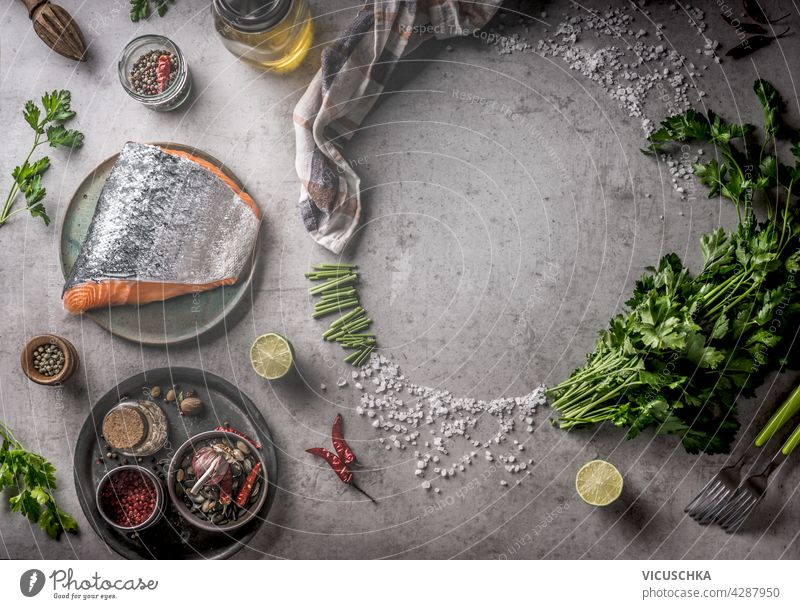 Frischer roher Lachs mit Rahmen von Gewürzen, Öl, frischen Kräutern und Zitrone auf grauem Beton Hintergrund. Kochen Vorbereitung mit frischen Zutaten zu Hause. Ausrüstung: Gabel, Schüsseln und Küchentuch. Ansicht von oben
