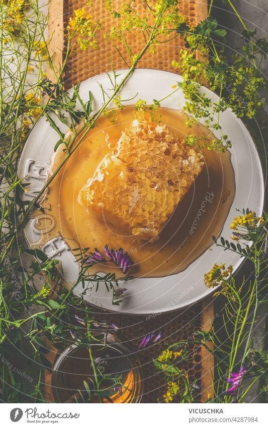 Frischer Honig mit Honigwaben auf einem Teller, umgeben von wilden Blumen und einem Glas. Natürliches, organisches Lebensmittelkonzept. Dunkler Beton-Hintergrund. Ansicht von oben