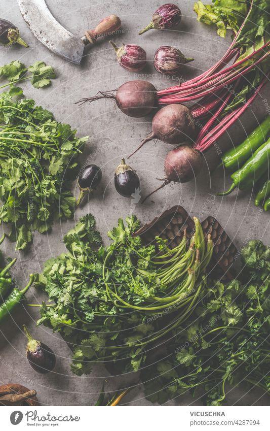 Frisches Bündel Rote Bete und Kräuter. Gemüse und Vintage-Küchenutensilien auf dunklem Beton Hintergrund. Kochen Vorbereitung mit frischem Gemüse. Gesundes Essen Konzept. Ansicht von oben