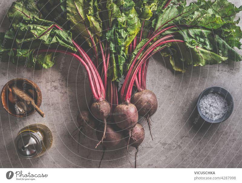Frisches Bündel Rote Bete mit grünen Blättern und Kochzutaten: Olivenöl, Salz und Knoblauch auf dunklem Betonhintergrund. Bio-Gemüse. Gesunde Ernährung Konzept. Ansicht von oben