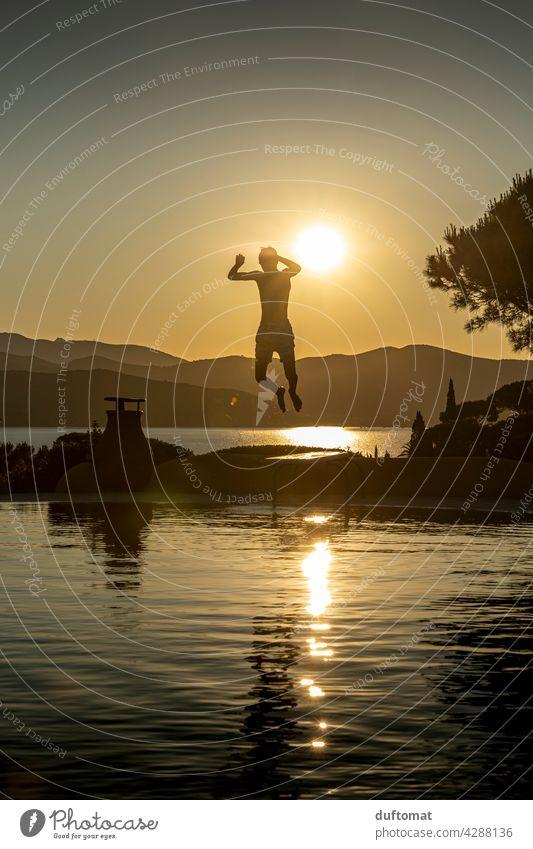 Teenager springt abends von Sprungbrett ins Wasser Abend Sonnenuntergang Pool Junge Gegenlicht Gegenlichtaufnahme Schwimmbad Schwimmen & Baden Freizeit & Hobby