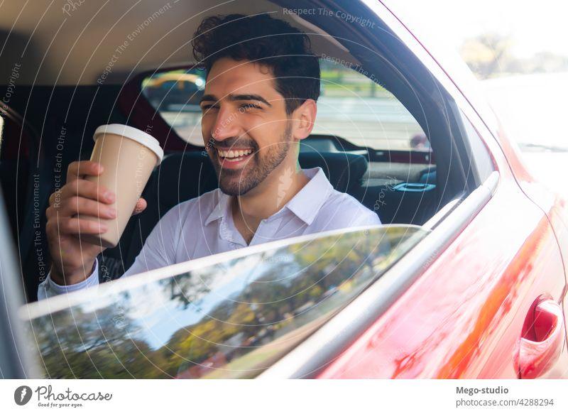 Geschäftsmann trinkt Kaffee im Auto. Mann PKW reisen Lifestyle Taxi professionell Transport Fahrzeug Rücksitz Nahaufnahme zum Mitnehmen stylisch elegant jung