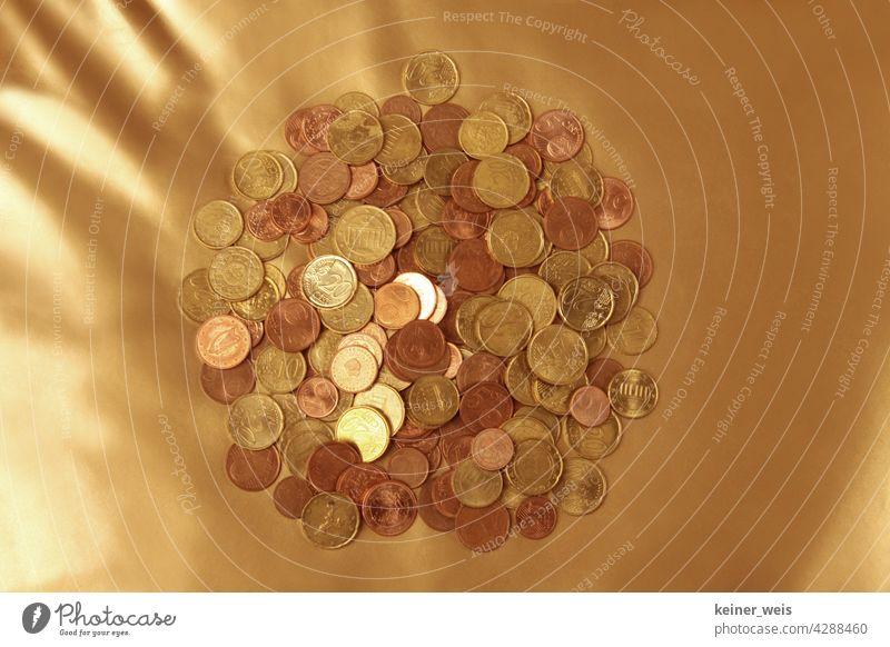 Viele Euro-Cent-Münzen auf einem goldenen Hintergrund - finanzielles Polster aus einem Haufen Kleingeld Geld Cents Geldmünzen bezahlen Kapitalwirtschaft