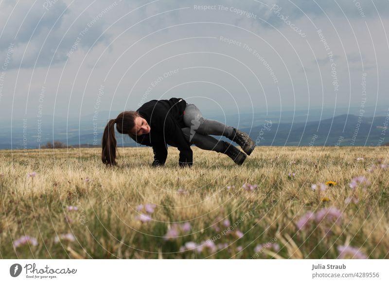 Yoga in der Rhön beim Wandern hochrhön Natur Naturschutzgebiet Wiese Wiesenblume Blume Pflanze Yogastellung Frühling wandern Wanderschuhe sportlich
