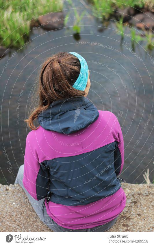 Junge Frau in sportlicher Kleidung sitzt auf einer Brücke am Bach sitzen Beton lange Haare braune Haare brünett Pferdeschwanz lila pink Natur Naturschutzgebiet