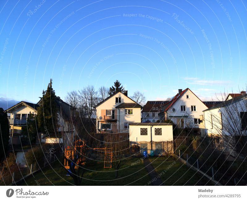 Typische Wohnhäuser mit Spitzgiebel als Eigenheim im Licht der untergehenden Sonne vor strahlend blauem Himmel in der hessischen Provinz in Wettenberg Krofdorf-Gleiberg bei Gießen in Mittelhessen