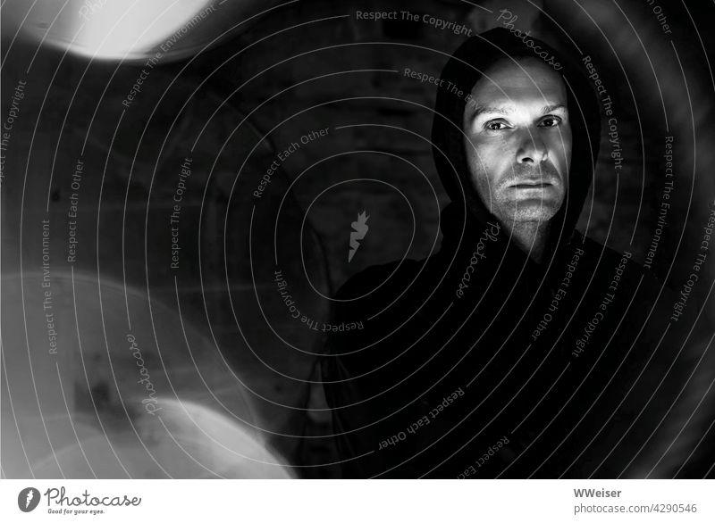 Ein ernst blickender Mann in dunkler Kleidung und Kapuze inmitten von atmosphärischen Störungen dunkel finster nachdenklich düster Mönch Kloster Mauern