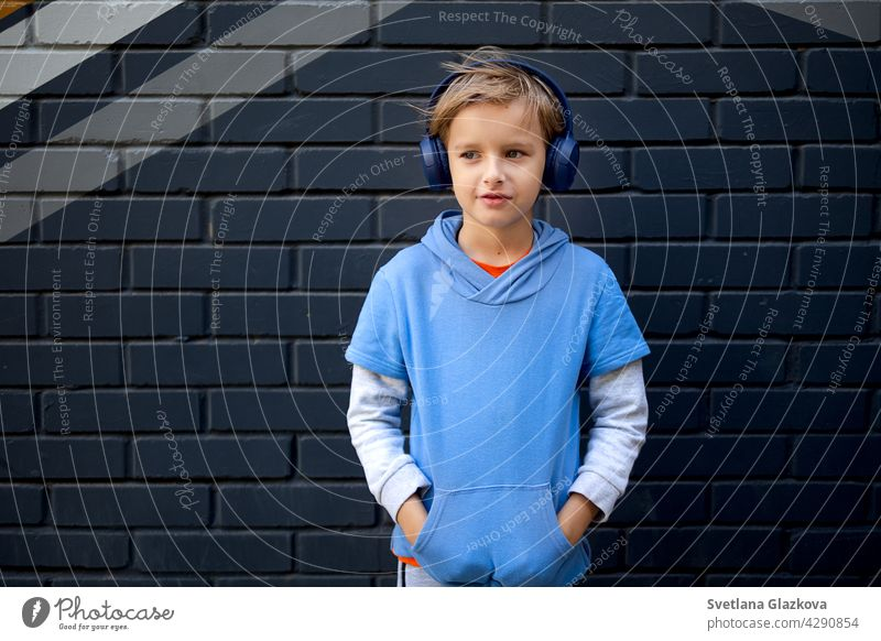 Blonde kaukasische Junge in einem blauen Kapuzenpulli und Kopfhörer steht auf einer Straße in der Stadt gegen eine graue Backsteinmauer, Musik hören in einer guten Stimmung