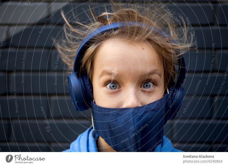 Lustiges Porträt eines blonden, kaukasischen Jungen, dessen Haare aufstehen und im Wind wehen. Schaut in die Kamera.gekleidet in einer schützenden medizinischen Maske und blaue Kopfhörer