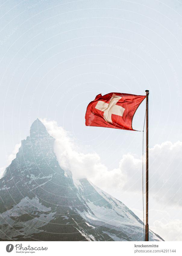 Schweizer Flagge im Wind vor Matterhorn Fahnenmast Nationalflagge Patriotismus wehen Himmel flattern Stolz Wolken blau Außenaufnahme rot Zermatt Wahrzeichen