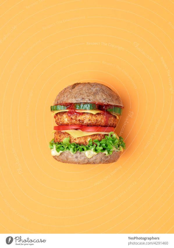 Veggie-Burger Draufsicht isoliert auf einem orangefarbenen Hintergrund. oben alternativ Brot Brötchen Käse Cheeseburger Farbe Konsumverhalten Küche ausschneiden