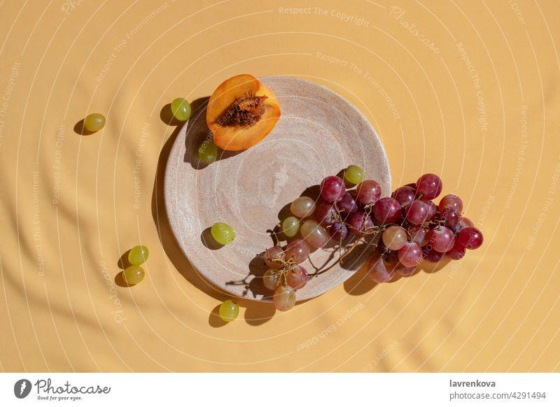Geschnittener frischer Pfirsich und Traube auf selbstgemachtem Keramikteller auf gelber Tischdecke, Früchte Catering Trauben Diät Vitamin Sommer Snack