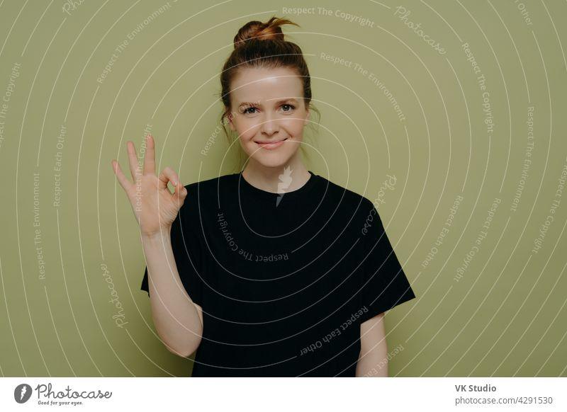 Ruhige Brünette Frau in schwarzem T-Shirt zeigt okay Zeichen Glück jung OK gestikulieren Mädchen Pose Lächeln Hintergrund Hand Person schön Teenager Porträt