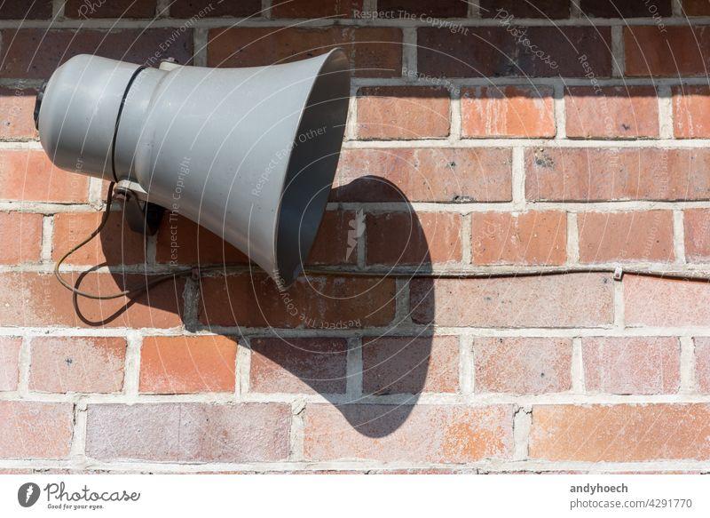 Megaphon vor einer alten Backsteinmauer Inserat Werbung Alarm wach ankündigen Ankündigung Aufmerksamkeit Hintergrund sich[Akk] hüten Backsteinwand
