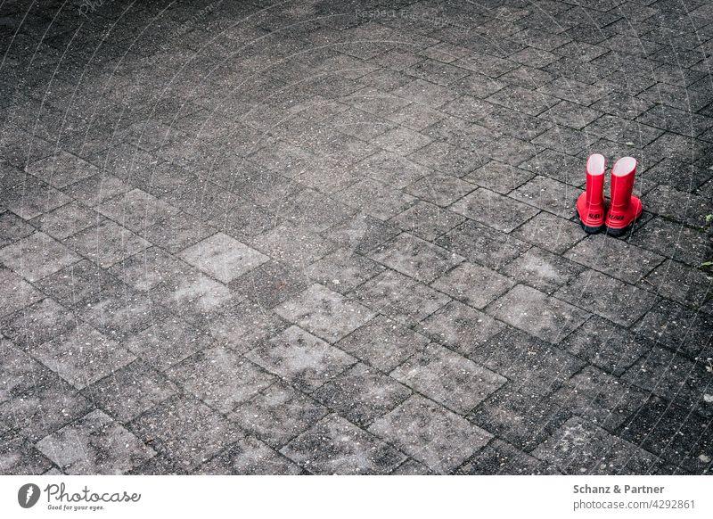 rote Gummistiefel auf Steinboden Pflastersteine Kindershuhe spielen Füße draußen versiegelt grau Außenaufnahme Farbfoto Menschenleer Straße Wege & Pfade