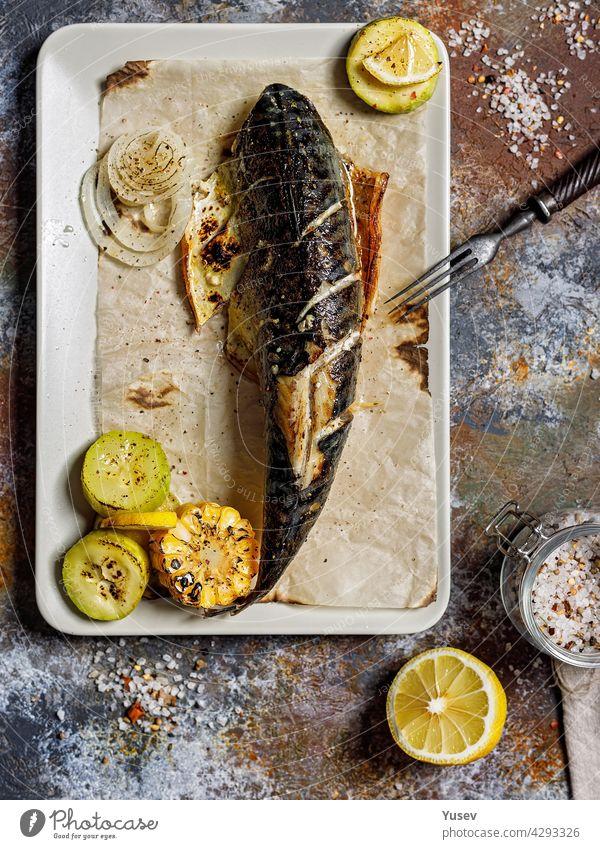 Draufsicht köstliche gegrillte Makrele mit Gemüse auf einer rechteckigen Platte. Appetitlicher gebratener Seefisch mit Mais, Zucchini und gewürzter Zitrone. Mediterrane Küche. Gesunde Meeresfrüchte. Vertikale Aufnahme