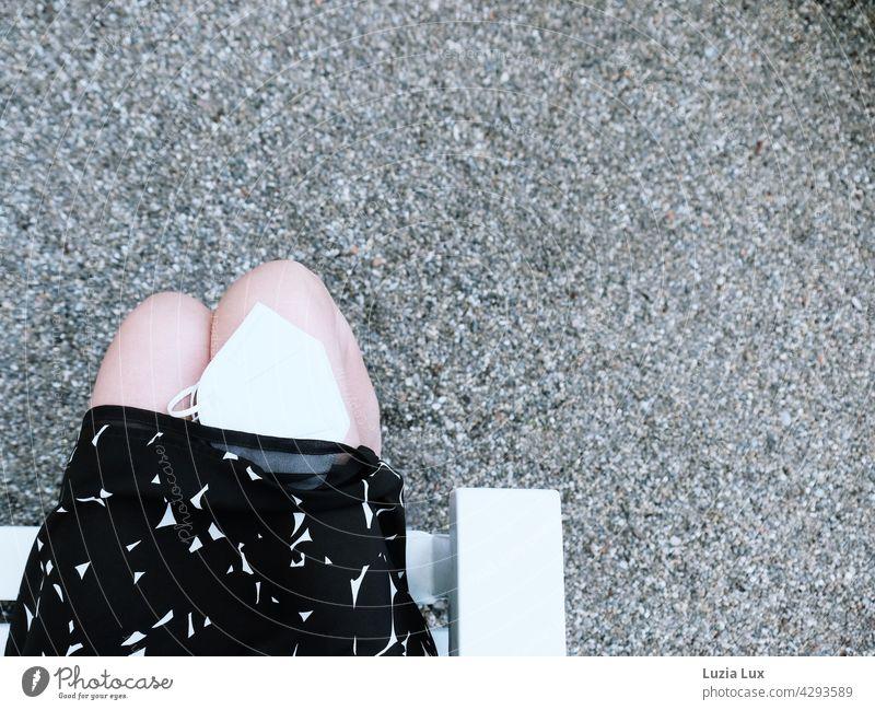 Sommer, Coronazeit: Frau im Kleid sitzt im Park, eine weiße Maske auf ihrem Knie ist halb unter den Rock gerutscht Frau mit Maske Gesichtsmaske Lifestyle