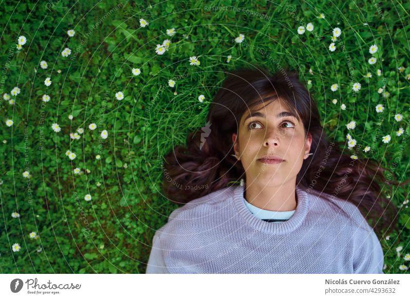 Hoffnungsvoll blickende junge Frau, die auf dem Gras liegt, umgeben von kleinen Blumen. Person Natur Lügen Erholung grün Porträt Textfreiraum Lächeln Kaukasier