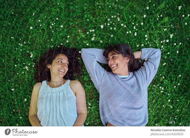 Zwei junge Frauen, die sich auf dem Boden liegend anschauen. echte Menschen Person Paar Glück Zusammensein Liebe lesbisch Lifestyle Freunde sich[Akk] entspannen