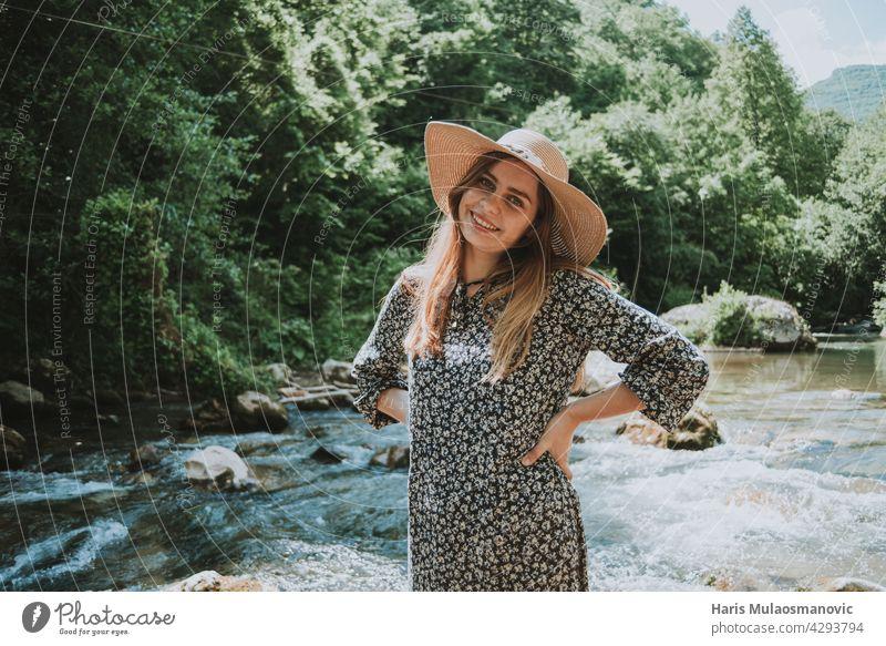 hübsche blonde Frau mit Hut am Fluss in der Natur Accessoire Erwachsener attraktiv weg von der Stadt schön Schönheit Brücke Kaukasier Kleid elegant Gesicht Mode
