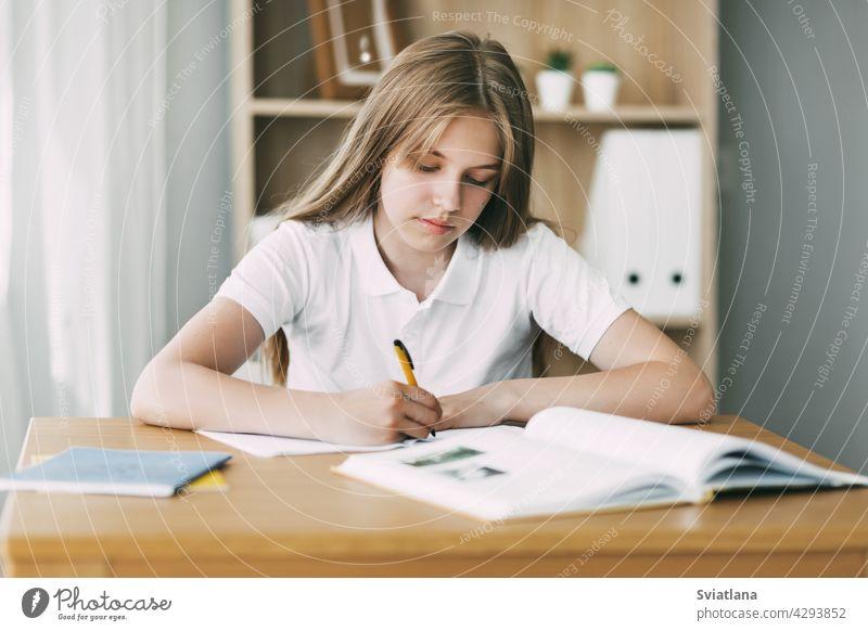 Ein Gymnasiast macht sich Notizen aus einem Buch, ein Teenager-Mädchen macht ihre Hausaufgaben und bereitet sich auf den Unterricht vor. Bildung, Ausbildung, Hausaufgaben