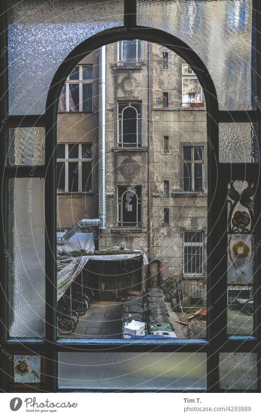 Blick durch das alte Treppenhausfenster auf den Hinterhof Friedrichshain Fenster Berlin Altbau unsaniert Trzoska window Haus Menschenleer Stadt Stadtzentrum