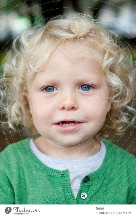 Kleiner Babyjunge mit lockigem Haar und blauen Augen Kind Kindheit Kleinkind gemütlich wenig weiß Junge im Freien klein Mode pulsierend Bekleidung schüchtern