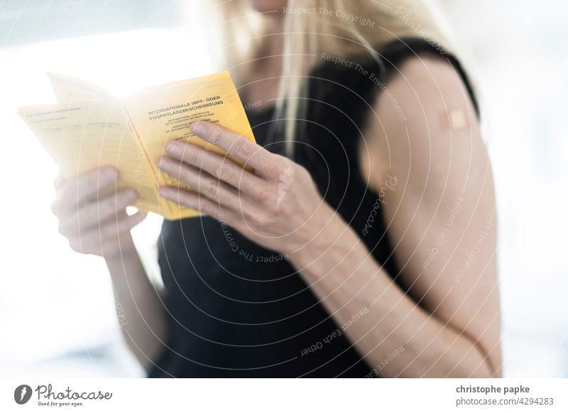 Blonde Frau hält impfausweis in der Hand und hat Pflaster auf Oberarm nach Impfung blond Impfausweis Corona coronavirus covid-19 Pandemie COVID Corona-Virus