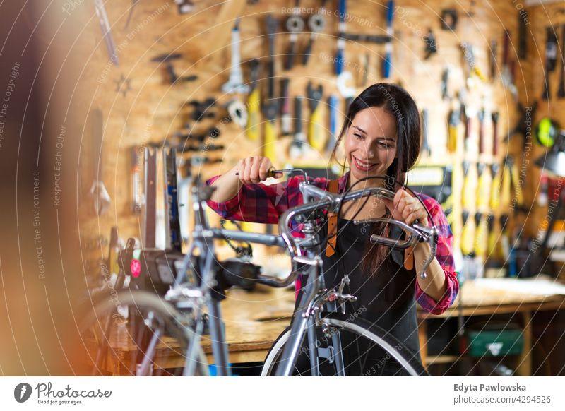 Junge Frau arbeitet in einer Fahrradwerkstatt Vertriebsmitarbeiter Fahrradmechaniker Radfahren Fahrradladen Business Einzelhandel Zyklus hilfreich