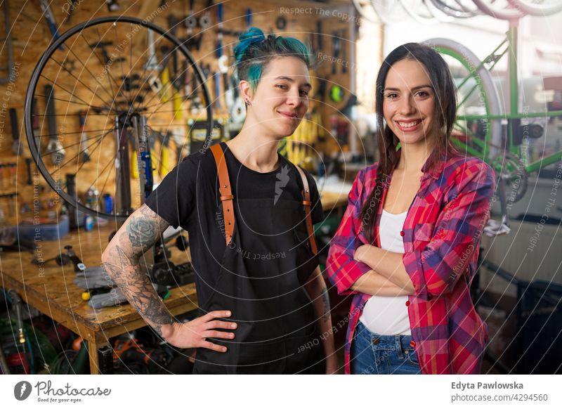 Zwei junge Frauen arbeiten in einer Fahrradwerkstatt Vertriebsmitarbeiter Fahrradmechaniker Radfahren Fahrradladen Business Einzelhandel Zyklus hilfreich